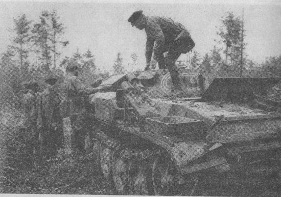Бойцы и командиры Красной Армии осматривают захваченный огнемётный танк противника. Хорошо видна установка дымовых гранатомётов на надгусеничной полке. Западный фронт, лето 1941 года.