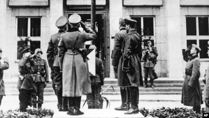 Немецкие и советские офицеры отдают салют флагу с нацистской свастикой во время парада в Брест-Литовске по случаю демаркации границы в Польше, 22 сентября 1939 года.